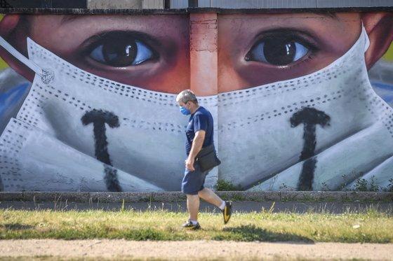 마스크를 쓴 남성이 대형 마스크 쓴 벽화를 배경으로 걷고 있다. 밀라노AP=ㅕ