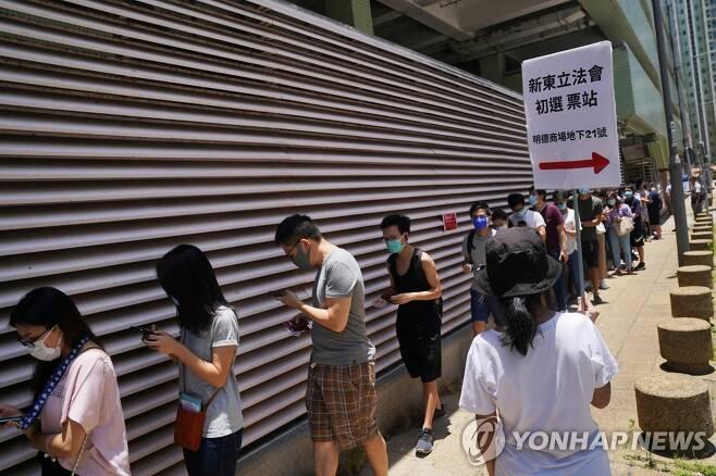 마스크 쓰고 예비선거 참여한 홍콩 유권자들 (홍콩 로이터=연합뉴스) 홍콩 범민주 진영이 지난 12일 실시한 입법회 예비선거의 투표장 앞에 신종 코로나바이러스 감염증(코로나19) 예방 마스크를 쓴 유권자들이 길게 줄지어 서 있다. 오는 9월 열리는 입법회 본 선거를 앞두고 범민주 진영의 후보군을 좁히기 위한 이번 예비선거는 11~12일 이틀간 치른다. sungok@yna.co.kr
