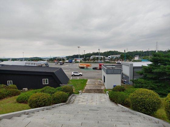 참전비 앞에서 바라본 휴게소 모습. 계단 왼쪽 건물이 행복장터다. 오른쪽은 수소가스 충전소. 김민욱 기자