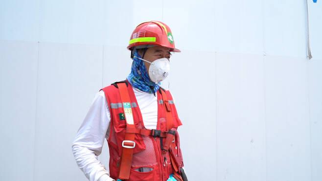 """건설노동자 이성원씨가 안전모에 마스크까지 착용한 모습. 그는 """"마스크를  하면 더 덥다""""고 말했다. 최유진 PD"""