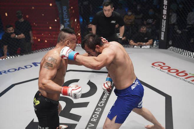 '소방관 파이터' 신동국(왼쪽)이 ARC 2회 대회에서 키르기스스탄 국가대표 레슬링 선수 출신의 소야트와 치열한 난타전을 벌이고 있다. 사진=ROAD FC