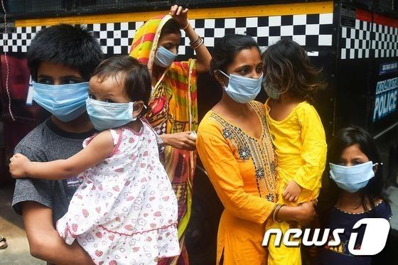 28일(현지시간) 인도 콜카타에서 마스크를 쓴 가족이 신종 코로나바이러스 감염증(코로나19) 검사를 받기 위해 기다리고 있다.  © AFP=뉴스1