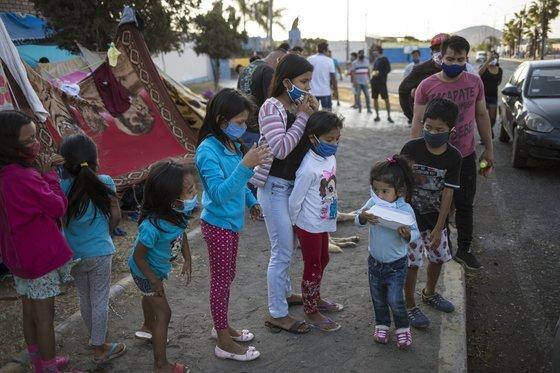 페루에서 신종 코로나로 인해 외출제한령이 내려졌던 약 3개월동안 여성 915명이 실종됐다. 여성 실종의 배경에는 심각한 가정 폭력이 있는 것으로 추정됐다. 지난 4월 페루 리마에서 코로나 방지를 위해 마스크를 낀 아이들이 무료 음식을 배급받기 위해 줄을 서 있다. [AP=연합뉴스]