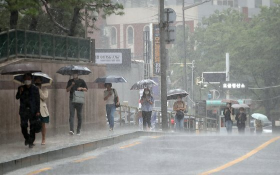 장맛비가 쏟아진 29일 오전 서울 중구 숭례문 인근에서 우산을 쓴 시민들이 발걸음을 재촉하고 있다. 연합뉴스