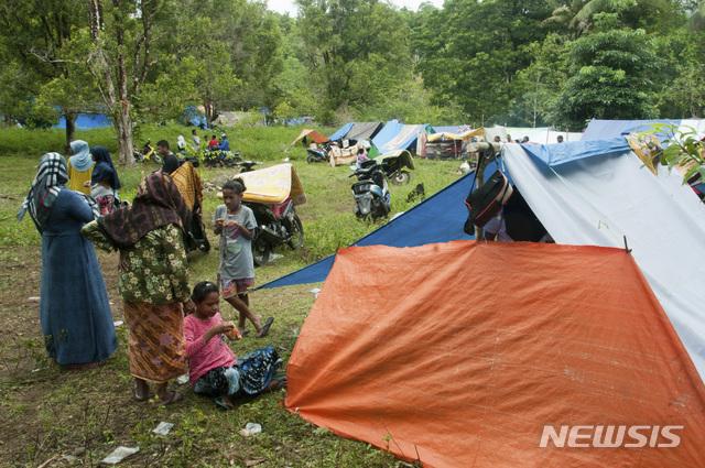 【암본(인도네시아)=AP/뉴시스】인도네시아 말루쿠주에 규모 6.5의 지진이 발생해 27일(현지시간) 암본섬 주민들이 임시대피소 텐트촌에서 생활하고 있다. 이번 지진으로 최소 20명이 숨지고 100여 명이 다쳤으며 암본섬 시내에서는 다리에 균열이 생기고 학교와 주택 등 수십 채가 파손되는 피해를 봤다. 2019.09.27.