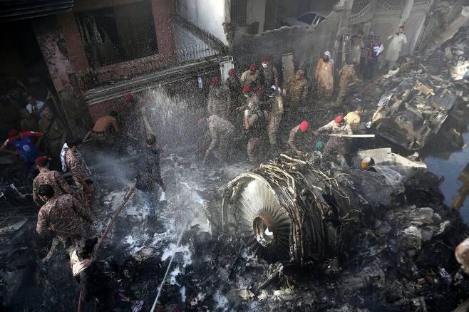 5월22일 파키스탄 남부 카라치의 여객기 추락사고 현장에서 의용 구조대원들이 생존자를 찾고 있다. 카라치/AP연합뉴스