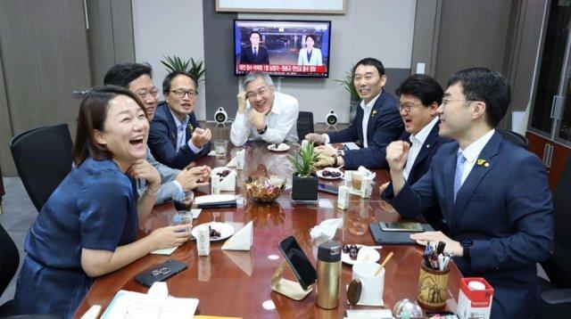 이재정·김승원·박주민·최강욱·김용민·황운하·김남국 의원이 최강욱 열린민주당 대표 의원실에서 '처럼회' 모임을 갖고 있다. 뒤에는 황운하 더불어민주당 의원의 지역구인 대전에서 폭우로 인해 사상자가 발생했다는 뉴스가 나오고 있다. 최강욱 열린민주당 대표 페이스북 캡처