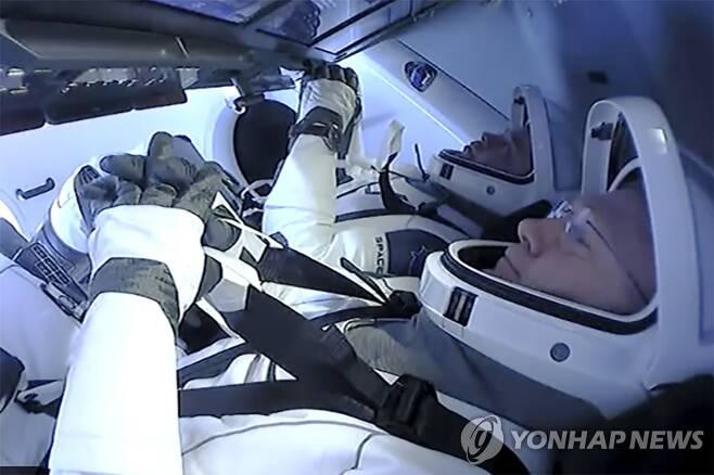 지구로 귀환 준비하는 NASA 우주비행사 (스페이스X AP=연합뉴스) 미국 항공우주국(NASA) 우주비행사 더그 헐리와 봅 벤켄이 2일(현지시간) 스페이스X 캡슐에서 지구로 귀환할 준비를 하고 있다. [NASA 제공] sungok@yna.co.kr