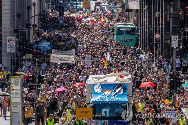'코로나19 규제'에 항의하는 독일 사람들 (베를린 AFP=연합뉴스) 신종 코로나바이러스 감염증(코로나19) 확산 방지를 위한 규제 조치에 항의하는 독일 시위대 수천 명이 1일(현지시간) 베를린 프리드리히 스트라스에서 '팬더믹 종말-자유의 날'이란 슬로건을 내걸고 거리 행진을 벌이고 있다. sungok@yna.co.kr