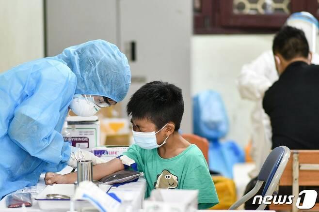 1일 베트남 하노이의 선별 진료소에서 보호복을 입은 의료진이 코로나19 검사를 위해 소년의 혈액 샘플을 채취하고 있다. © AFP=뉴스1