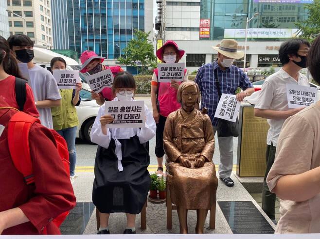 """소녀상을지키는부산시민행동이 지난 11일 오후 부산 동구 일본총영사관 인근 소녀상 앞에서 기자회견을 열어 총영사 발언을 규탄하고 있다. 동구 등에 따르면 일본 총영사는 동구청장을 찾아와 """"시민단체 점용 허가 요청을 수용한 것은 유감스럽다. 위안부상의 합법화와 고정화를 초래하는 행위""""라며 """"한일관계를 심각하게 훼손하는 만큼 허가를 취소해달라""""고 요청했다. [연합]"""