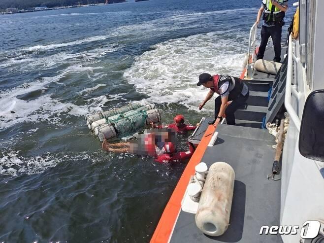 군산해경이 스티로폼 뗏목에 매달려 표류하던 관광객을 구조하고 있다. /© 뉴스1