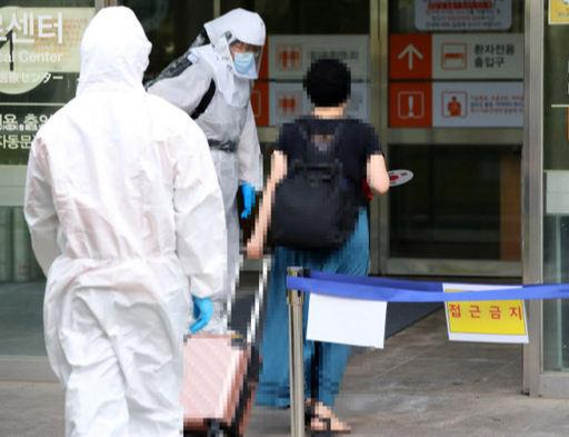 19일 오후 서울 중랑구 서울의료원에서 태극기 부채를 든 코로나19 환자가 입원을 위해 건물로 들어가고 있다. 연합뉴스