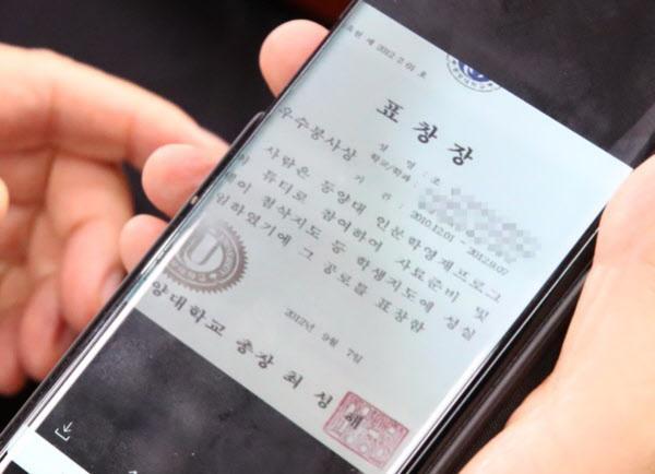지난해 9월 6일 조국 전 장관 인사청문회에서 박지원 의원이 조민씨가 받은 것으로 알려진 '동양대 표창장' 사진을 보고 있다/연합뉴스