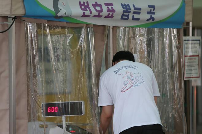 20일 오후 인천시 남동구 보건소 선별진료소에서 코로나19 검사를 받으려는 한 시민이 번호표를 뽑고 있다. 연합뉴스