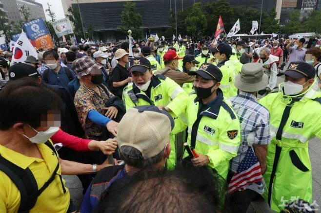 보수단체 집회 참가자들이 지난 15일 오전 서울 종로구 광화문광장에서 8·15 광복절 맞아 집회에 참석하기 위해 바리케이드를 밀고 경찰과 대치하고 있다.(사진=이한형 기자)