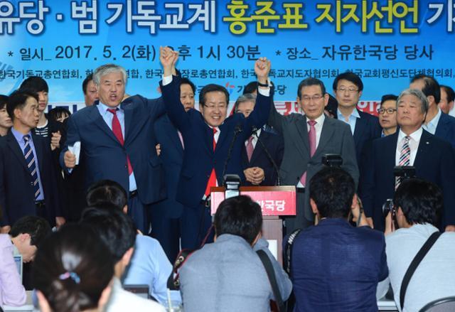 2017년 5월 2일 홍준표(가운데) 당시 자유한국당 대선후보가 서울 여의도 당사에서 열린 기독자유당ㆍ범기독교계 홍준표 지지 선언 기자회견에 참석, 전광훈(왼쪽 두 번째)목사와 손을 들고 인사를 하고 있다. 한국일보 자료사진