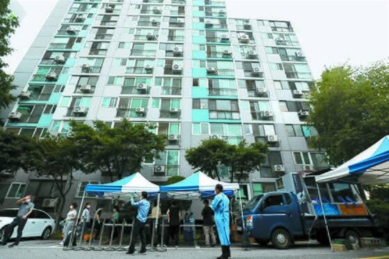코로나19 집단감염이 발생한 서울시 구로구의 한 아파트에서 26일 오후 보건소 직원들이 이동형 선별진료소를 설치하고 아파트 주민을 대상으로 진단검사를 실시하고 있다. [뉴시스]