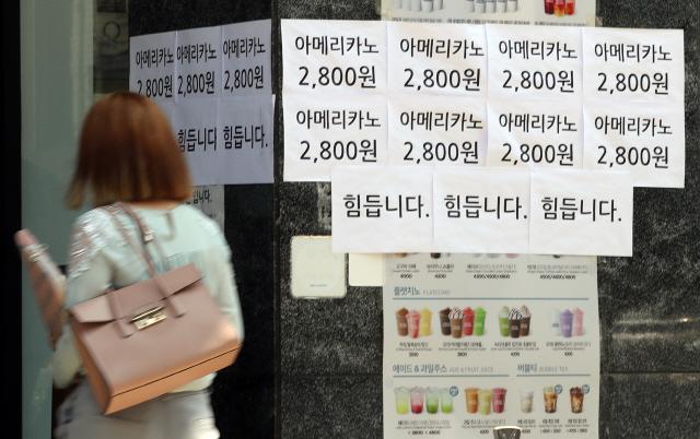 최근 수도권의 신종 코로나바이러스 감염증(코로나19) 확산으로 인한 강화된 2단계 사회적 거리 두기로 자영업자들의 시름이 깊어지는 가운데 1일 서울의 한 커피전문점에 '힘듭니다'라고 적혀있는 문구 앞으로 행인이 지나가고 있다. /연합뉴스