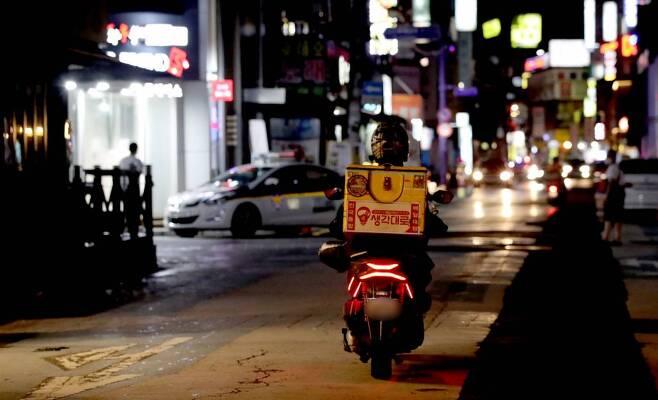 [서울=뉴시스] 박미소 기자 = 신종 코로나바이러스 감염증(코로나19) 확산 방지를 위해 수도권 지역의 사회적 거리두기 2.5단계가 시행된 30일 오후 9시 이후 서울 송파구의 음식점 골목에서 한 배달기사가 오토바이를 타고 지나고 있다. 2020.08.30.    misocamera@newsis.com
