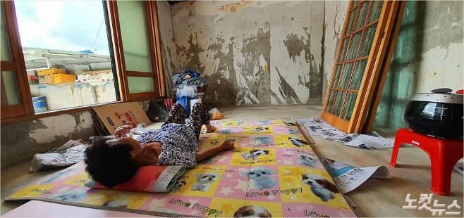 3일 오후 전북 남원시 금지면 하도마을, 조봉금(70)씨가 시멘트 바닥 위에 신문지와 매트리스를 깔고 누워 있는 모습. (사진= 남승현 기자)