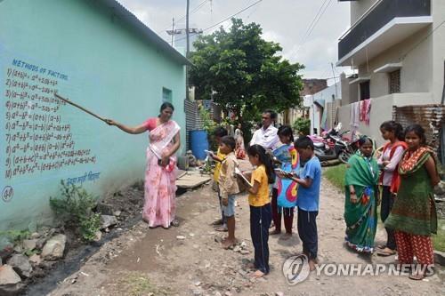 인도 마하라슈트라주의 한 학교 교사가 온라인 수업을 받을 수 없는 아이들을 위해 담벼락을 칠판 삼아 가르치고 있다. [AFP=연합뉴스]