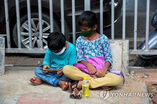 인도 하이데라바드에서 바닥에 앉아 코로나19 테스트를 기다리는 어린이들. [AFP=연합뉴스]
