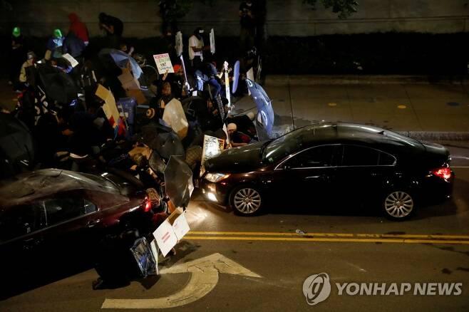 시위대를 향해 달려든 자동차 [로이터=연합뉴스]