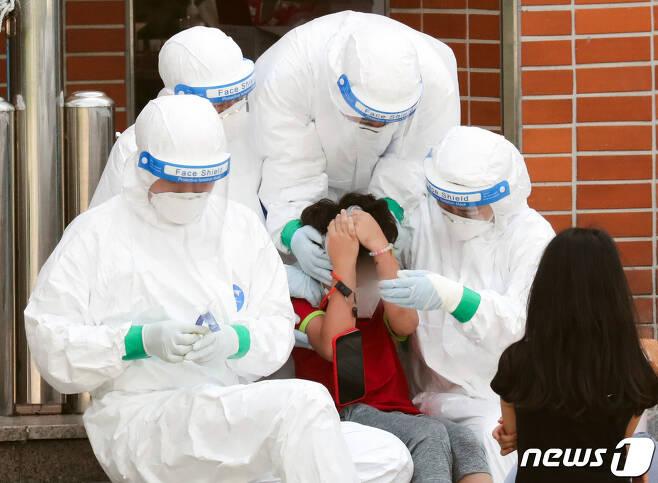 선별진료소에서 한 학생이 의료진의 도움을 받으며 검사를 받고 있다.  /뉴스1 © News1 허경 기자