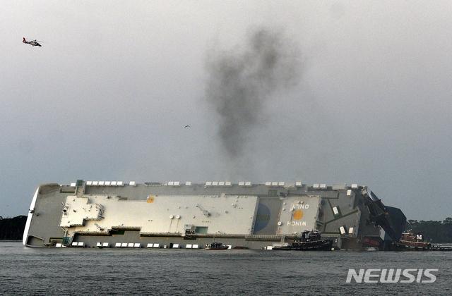[AP/뉴시스] 지난 해 9월8일 뒤집힌 골든 레이호에서 연기가 솟아오르고 있다. 승무원들은 모든 연료를 다 빼낸 뒤 배에서 탈출했고 이 배의 처리 문제는 일단 올해 10월초부터 절단, 철거하는 방향으로 결정되었다.
