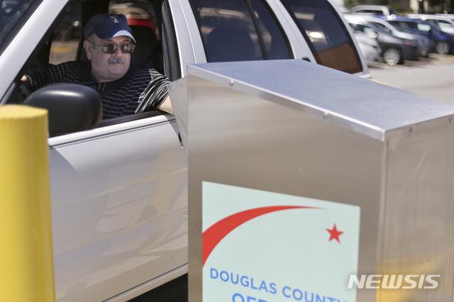 [오마하=AP/뉴시스] 미국 네브래스카주 오마하에서 한 남성이 19일 우편투표 신청 용지를 무인신청함에 투입하고 있다. 2020.8.27.