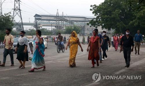 인도 뉴델리 외곽의 한 공장에서 퇴근하는 근로자들. 상당수가 마스크를 착용하지 않았다. [EPA=연합뉴스]
