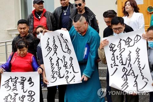 지난달 31일 몽골 울란바토르 외교부 밖에서 몽골어로 쓴 플래카드를 든 시위 참가자들이 중국에 항의하고 있다. [로이터=연합뉴스]