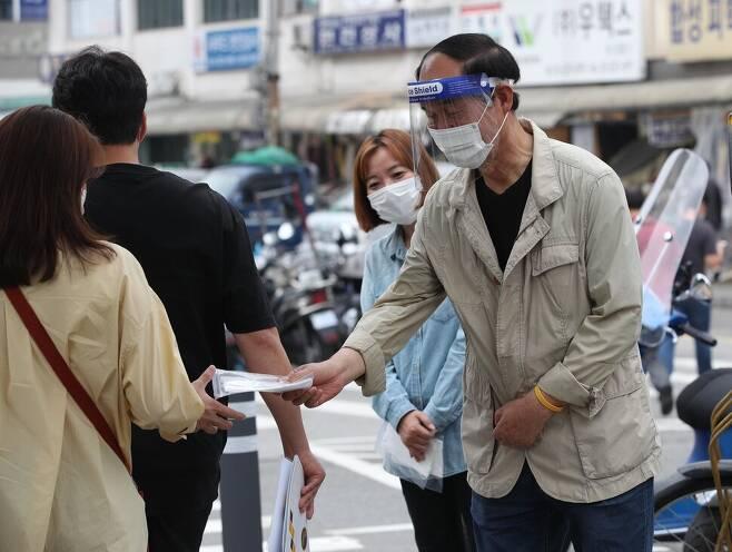 16일 오전 서울 종로구 전태일다리에서 열린 '제16차 전태일 50주기 캠페인'에서 이수호 전태일 재단 이사장이 시민들에게 마스크를 나눠주고 있다. 김봉규 선임기자