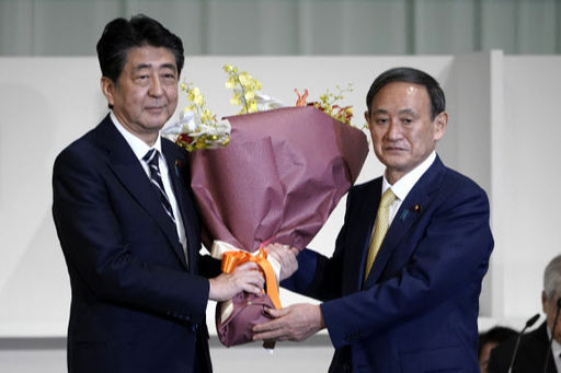 퇴임을 앞둔 아베 신조 일본 총리가 지난 14일 도쿄도 미나토구의 한 호텔에서 진행된 자민당 총재 선거 투개표에서 차기 총재로 선출된 스가 요시히데 관방장관에게 꽃다발을 건네고 있다. AFP연합뉴스
