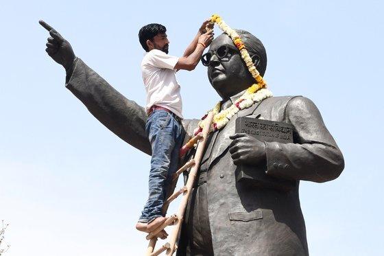 카스트 차별을 금지한 인도 헌법을 만든 인도의 전 법무장관인 빔라오 람지 암베드카르(그림 속 인물)는 인도 불가촉천민들에게는 영웅으로 추앙받는다. 그를 본따 만든 동상에 꽃 목걸이를 걸고 있는 인도 남성. [AFP=연합뉴스]