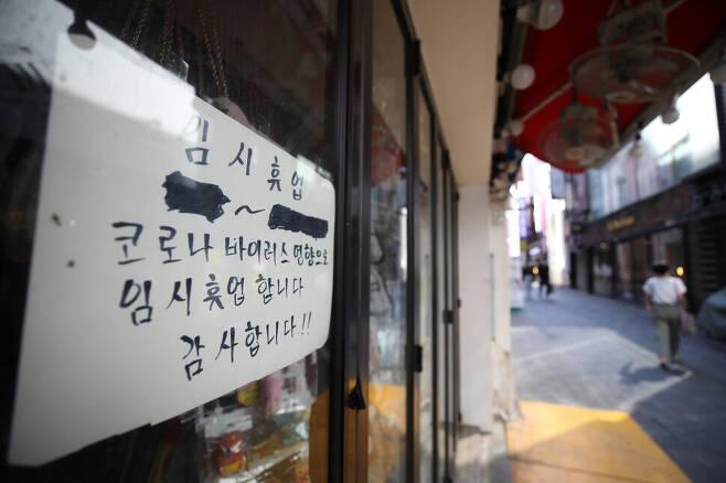 20일 서울 명동거리의 한 가게에 코로나19로 인한 임시휴업 안내문이 붙어 있다. 연합뉴스