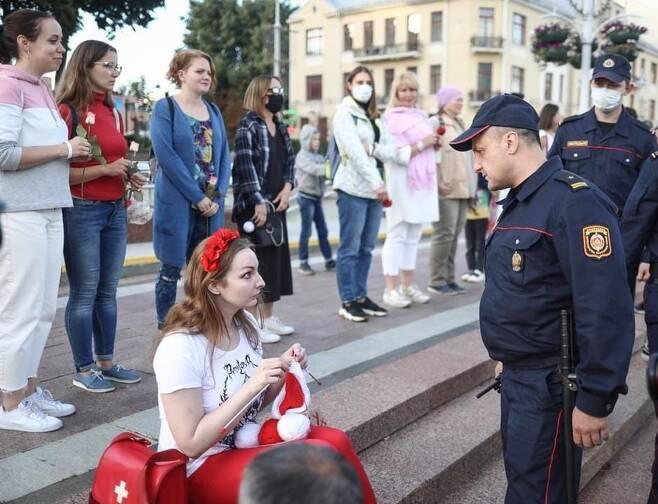 경찰이 다가오자 한 벨라루스 여성이 뜨개질하고 있다./트위터