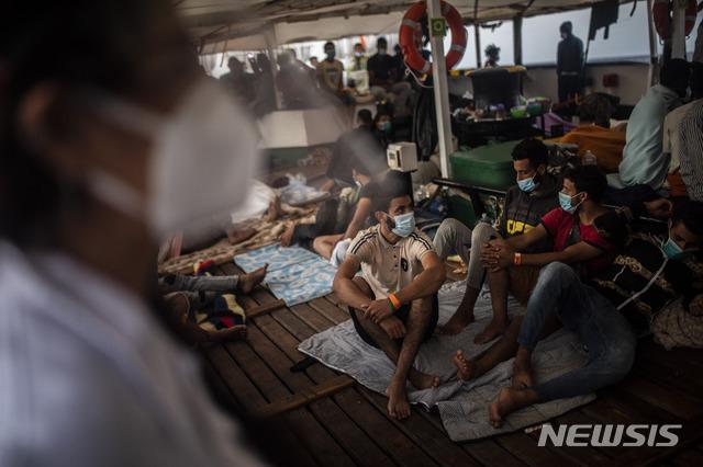 [트리폴리=AP/뉴시스] 지중해의 리비아 해역에서 구조된 유럽행 난민들이 지난 9월9일 배 안에서 마스크를 쓴채 대기하고 있다.2020.09.14