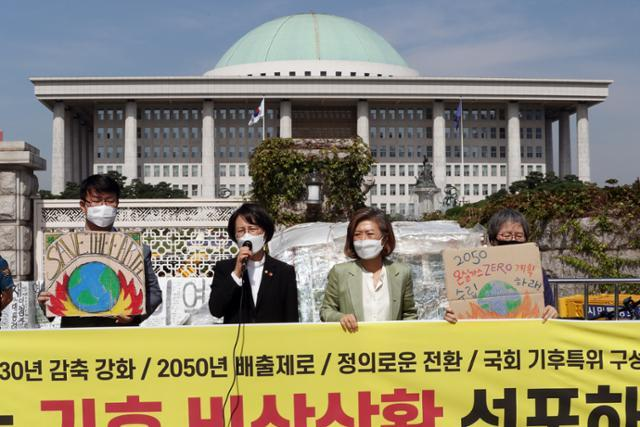 강은미(왼쪽 두 번째) 정의당 의원이 양이원영(왼쪽 세 번째) 의원과 함꼐 21일 오전 서울 여의도 국회 앞에서 기후위기비상행동과 함께 가진 국회 기후 비상선언 결의안 채택을 촉구하는 기자회견에서 발언을 하고 있다. 뉴스1