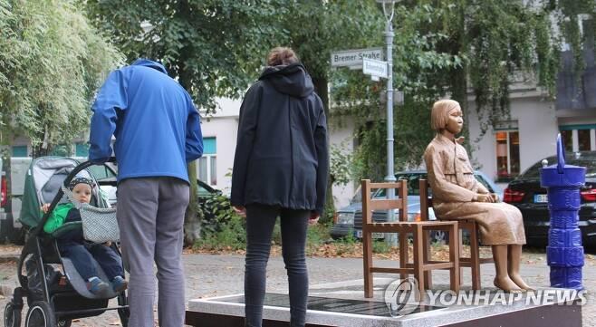 베를린 거리에 설치된 소녀상 비문을 읽는 시민들 (베를린=연합뉴스) 이광빈 특파원 = 지난 25일(현지시간) 독일 수도 베를린에 설치된 '평화의 소녀상'에 쓰인 비문을 지나가던 시민들이 읽고 있다. 2020.9.27 lkbin@yna.co.kr