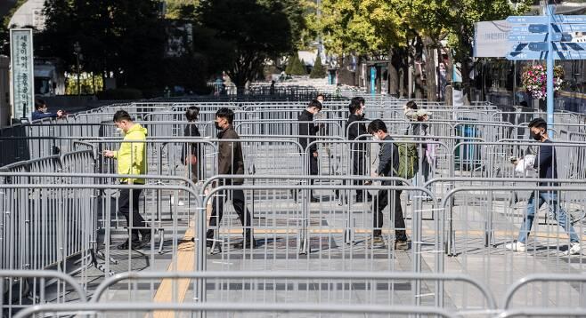 한글날인 9일 서울 광화문 일대에 차벽과 펜스가 설치되어 있는 가운데 세종문화회관 앞에서 시민들이 미로를 걷듯 발걸음을 옮기고 있다./ 고운호 기자