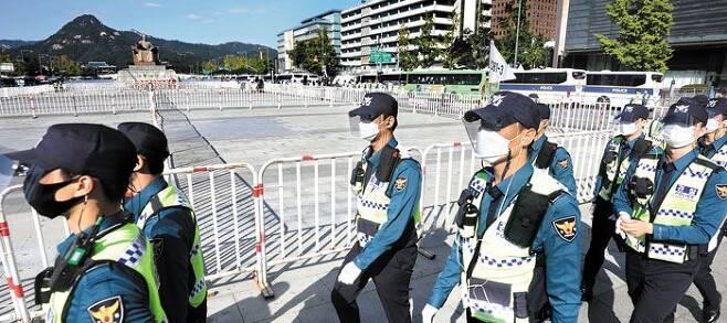 한글날, 펜스에 갇힌 세종대왕 - 한글날인 9일 오후 서울 종로구 광화문광장을 겹겹이 에워싼 철제 펜스 옆으로 마스크를 쓴 경찰관들이 줄을 지어 이동하고 있다. 일반 시민들은 광화문광장에 있는 세종대왕상 근처로 접근하는 것이 금지됐다. 경찰은 이날 광화문광장 일대에 경찰관 1만2000명을 배치해 시민들의 통행을 제한했다. /장련성 기자