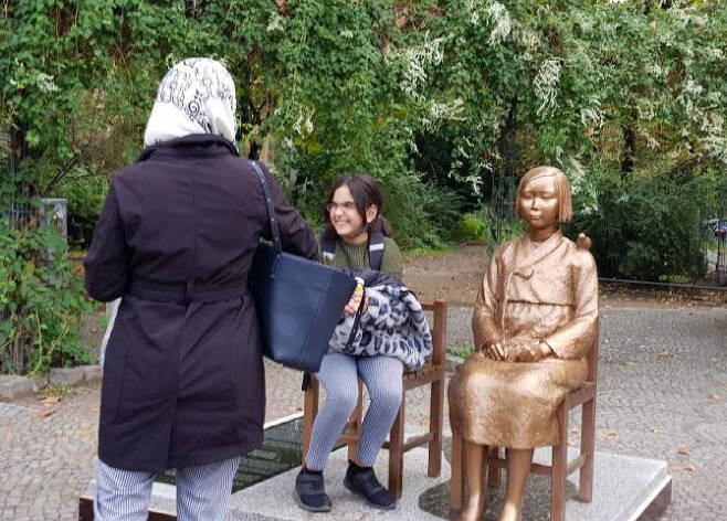 지난 9월 25일(현지시간) 독일 수도 베를린에 설치된 '평화의 소녀상' 옆에 한 소녀가 앉아있다. (사진=연합뉴스)