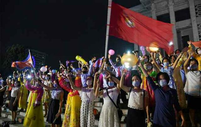 지난 8월 28일, 평양 문화회관 광장에서 진행된 청년절을 맞아 마스크를 쓴 북한 청년들이 손을 흔들며 공연을 관람하고 있다. 뉴스1