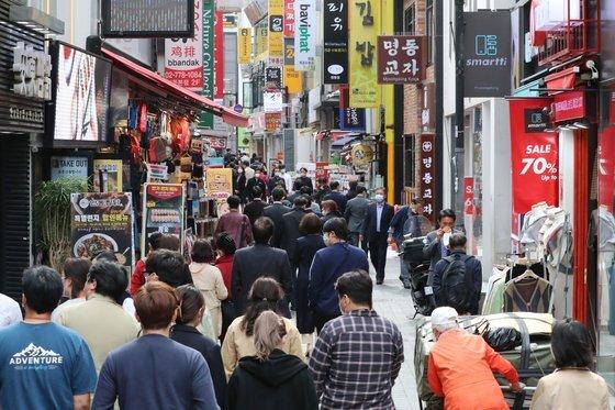사회적 거리두기 1단계 전환 사흘째인 지난 14일 오후 서울 명동거리가 점심 식사를 위해 이동하는 직장인들로 붐비고 있다. 연합뉴스