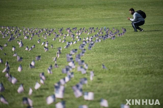 [워싱턴=신화/뉴시스]22일(현지시간) 미국 워싱턴 DC의 내셔널 몰에서 한 남성이 하는 코로나19로 사망한 희생자 20만 명을 상징하는 미국 국기를 사진으로 찍고 있다. 미 존스홉킨스대 시스템과학공학센터(CSE)는 미국의 코로나19 누적 확진자 수는 709만7937명, 사망자는 20만5471명이라고 발표했다. 2020.09.23.