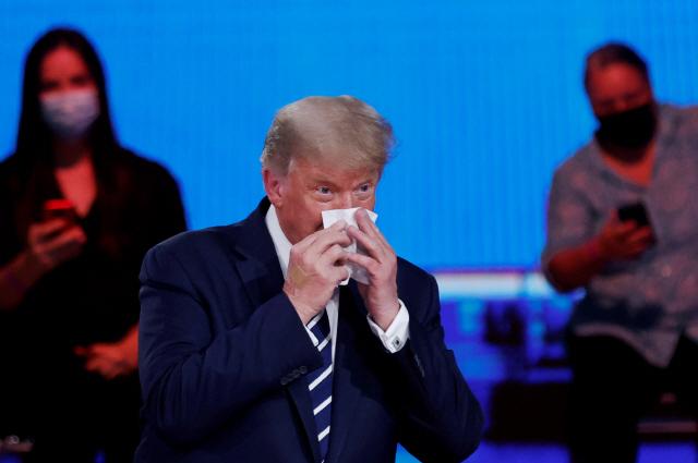 도널드 트럼프 미국 대통령이 15일(현지시간) 플로리다주 마이애미에서 열린 NBC방송과의 타운홀 행사 도중 코를 풀고 있다. 트럼프 대통령은 이날 행사에서 마스크를 쓰지 않았다. /로이터연합뉴스