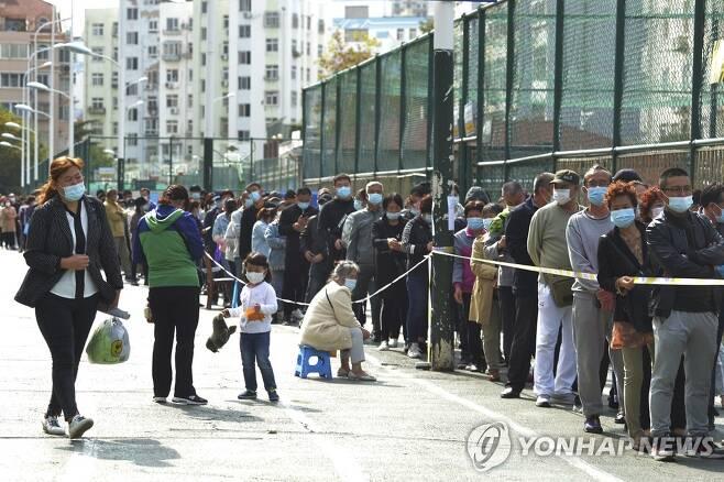 중국 칭다오의 코로나19 핵산검사 행렬 (칭다오 AP=연합뉴스) 12일 중국 산둥성 칭다오의 주거지역 인근에서 마스크를 쓴 시민들이 신종 코로나바이러스 감염증(코로나19) 핵산검사를 받기 위해 길게 줄을 서 있다. 이날 칭다오시 위생건강위원회는 전날 오후 11시 현재 6명의 코로나19 확진 환자와 6명의 무증상 감염자가 발생했다고 발표했다. 상주인구가 1천만명에 가까운 칭다오시는 곧바로 전 주민 대상 핵산검사에 착수했다. leekm@yna.co.kr