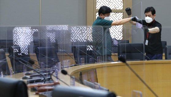 지난 8월 세종시 정부세종청사 국무회의장에 관계자들이 코로나19 감염 예방을 위한 비말 차단 투명 칸막이를 설치하고 있다. 연합뉴스